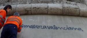 """Unos operarios limpian una pintada con el lema """"Primavera valenciana"""" en las torres de Quart."""