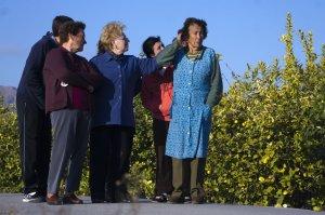 Carmen Calderón, a la derecha, en el lugar donde fueron asaltadas; una vecina le mira el hematoma en la cabeza.
