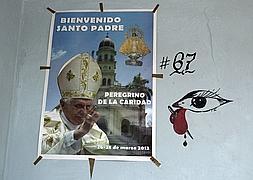 Cartel de bienvenida al Papa junto a un ojo de santería en el poblado El Cobre, Santiago de Cuba.