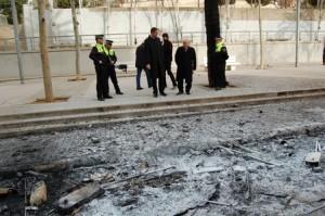 El alcalde Xavier Garcia Albiol, rodeado de agentes de la policía local, ante restos de contenedores quemados.