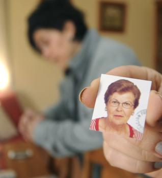 Una de las hijas de la fallecida muestra una foto de su madre, en presencia de su hermana.