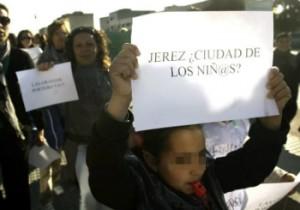 """Una niña del colegio """"Las Granjas"""" de Jerez de la Frontera (Cádiz) acompañada por sus padres, lleva un cártel de protesta durante la manifestación que bajo el lema """"La Educación no es basura""""."""