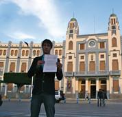 José Valdivieso muestra la denuncia; a su espalda, el Palacio de la Asamblea de Melilla.