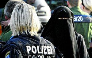 Una policía observa a una musulmana durante una concentración islamista en Fráncfort para escuchar a un predicador islámico.