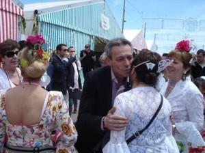 Anglada saluda a un grupo de mujeres bellamente ataviadas con trajes de faralaes.