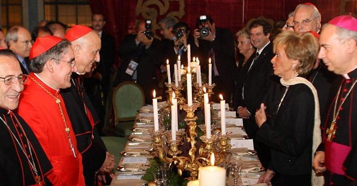 El arzobispo de Barcelona, de rojo, entre los prelados que agasajan a la ex vicepresidenta del Gobierno de Zapatero, María Teresa Fernández de la Vega.