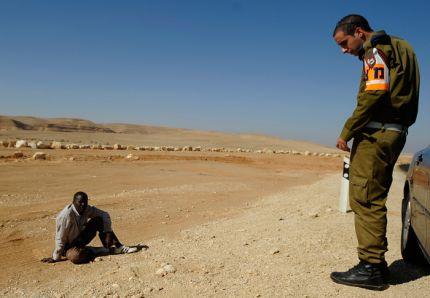 Un soldado israelí monta guardia ante refugiado sudanés, cerca de la frontera con Egipto.