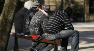 Jóvenes, sentados en un banco, en una foto de archivo
