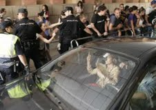 Entre varios agentes de policía, Andrea Fabra lanza un gesto obsceno a un grupo de ciudadanos.