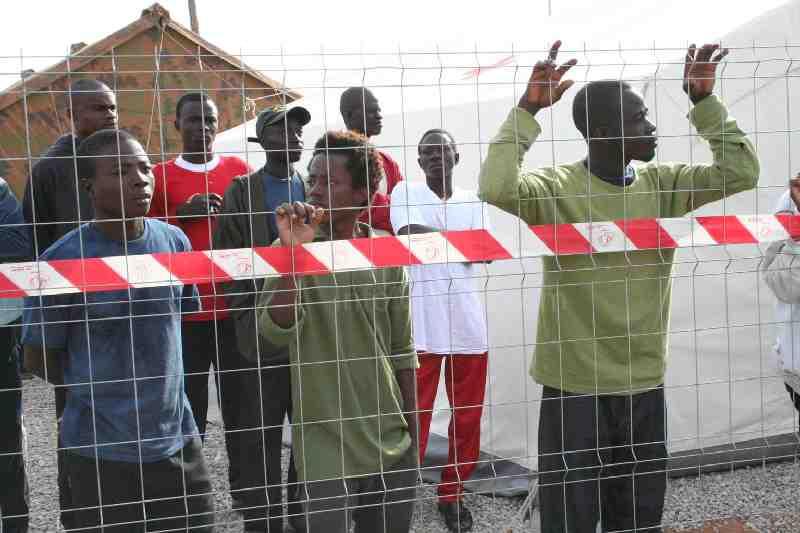 Subsaharianos esperan la llegada de la noche para asaltar la valla fronteriza de Melilla.