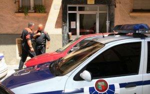 Dos agentes de la Ertzaintza hacen guardia ante la casa donde ocurrieron los hechos.