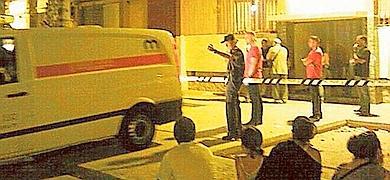El furgón policial ante el portal acordonado.