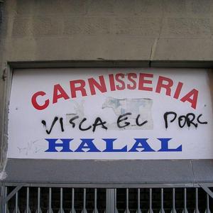 """""""Visca el porc"""", reza pintado a mano en el cartel de una tienda halal en Cataluña."""