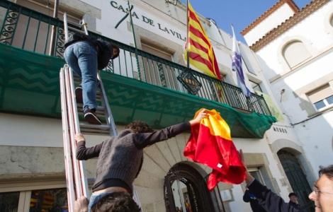 Un grupo de delincuentes separatistas retira una bandera de española del balcón de un Ayuntamiento catalán.