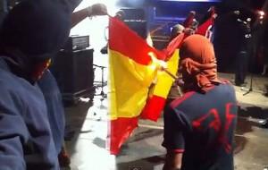 Separatistas catalanes se disponen a quemar una bandera de España.
