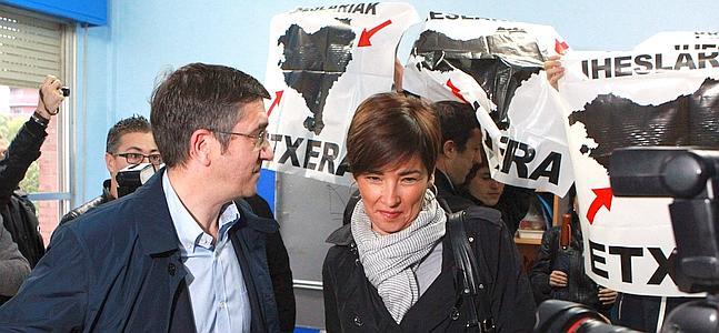 Un grupo de personas recibe con carteles de presos de ETA al lehendakari y su esposa.