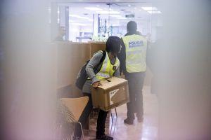 Una policía transporta una caja en el registro a unas dependencias del Ayuntamiento de Sabadell.