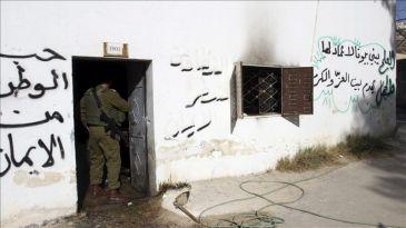 Un soldado israelí revisa los daños registrados en una escuela en la que han hecho pintadas.