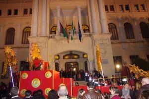 La carroza del rey Gaspar, de vuelta ya vacía, pasa delante del Ayuntamiento con las banderas a media asta.
