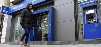 Una mujer camina junto un banco chipriota.
