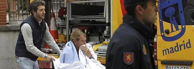 Un enfermo es desalojado de la clínica madrileña de La Milagrosa.