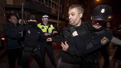 El hombre que llevaba el líquido inflamable, retenido por policías.