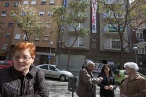 Ana, a la izquierda, propietaria de dos pisos en el edificio 'ocupado' en Nou Barris, al fondo.