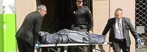 Efectivos de los servicios funerarios trasladan el cuerpo de la mujer.