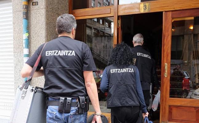 Ertzainas de la Policía Científica entran en el portal.