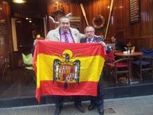 Armando Robles y Gerard Bellalta posan con una bandera española con el águila de San Juan tras el homenaje tributado al director de AD por casi tres centenares de catalanes.