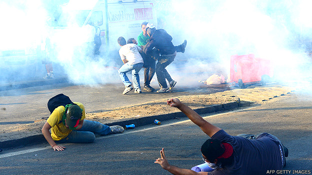 Río de Janeiro. Manifestantes se protegen del gas lacrimógeno fuera del Estadio Maracaná este 16 de junio.