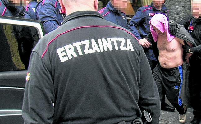 Agentes de la Ertzaintza sacan al detenido del gimnasio, donde hallaron a la mujer en parada cardiorrespiratoria.