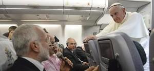 Francisco escucha la pregunta de uno de los periodistas en el avión que le traslada a Italia.