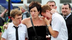 Dos niños lloran durante la repatriación de los cuerpos de siete soldados británicos muertos en Afganistán, en Wootton, Reino Unido