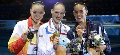 Carbonell (d), muestra su medalla de bronce junto a Huang (i) y Romashina.