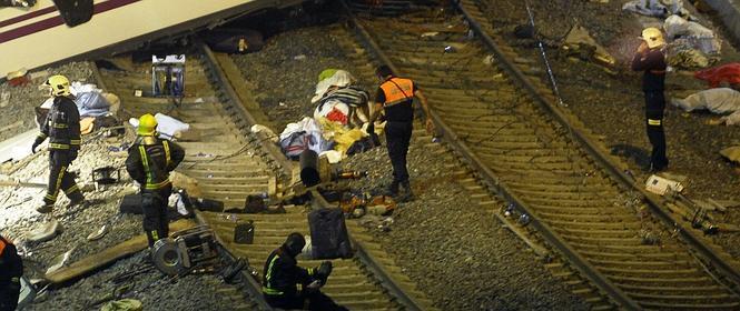 Cuerpos recuperados del tren cubiertos con mantas en el lugar del siniestro.