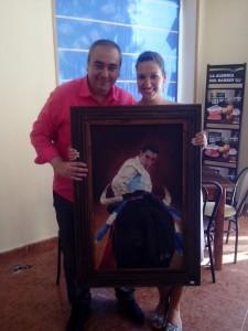 Armando Robles y la jefa de producción de 'La Ratonera', Lucía Gálvez, posan con el cuadro del diestro granadino en plena faena de muletas..