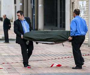Dos operarios trasladan el cadáver de una española de Baracaldo que iba a ser desalojada de su casa.