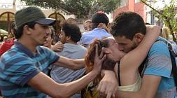 Una pareja participante en el acto se besa al tiempo que otro hombre les empuja para evitarlo.