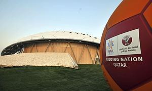 Logotipo de la candidatura de Catar 2022 para el mundial de fútbol junto a un estadio en Doha (Catar),