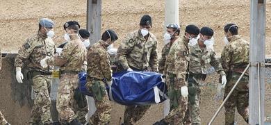 Varios militares italianos trasladan el cadáver de una de las víctimas del naufragio .