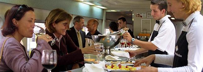 Camareros atienden a clientes en el bar de un tren de Renfe.