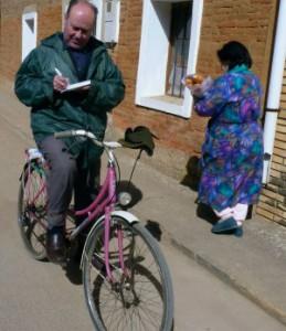 El Padre Jesús Calvo recorre en bicicleta las calles de Villamuñio (León) para tomar nota de las necesidades de sus parroquianos