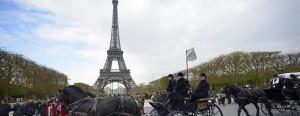 Un coche de caballos cruza por delante de la torre Eiffel de París.