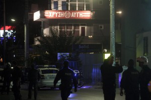 Policías delante del local del partido Amanecer Dorado, donde dos hombres han sido asesinados a balazos este viernes