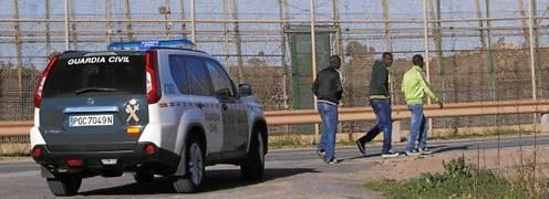 Tres inmigrantes pasean junto a la frontera de Melilla ante la atenta mirada de una patrulla de la Guardia Civil