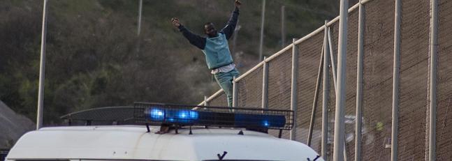 Un inmigrante encaramado a la valla de Melilla.