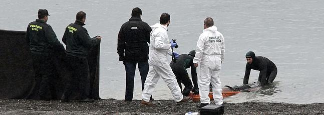 Agentes de la Guardia Civil recuperan el cadáver de uno de los fallecidos.