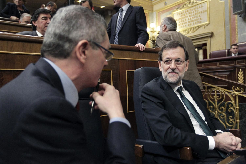El presidente del Gobierno, Mariano Rajoy, dialoga con el ministro de Justicia, Alberto Ruiz-Gallardón, en el Congreso.