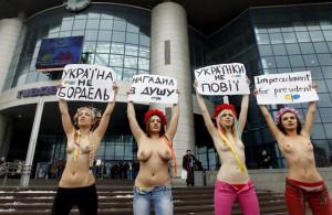 """Militantes del movimiento femenino """"Femen"""", portan pancartas con sus torsos desnudos durante una protesta frente a la estación de trenes en Kiev, Ucrania"""